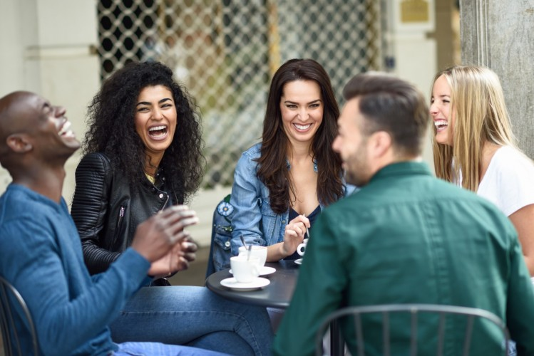 Multiracial group of five friends having a coffee together. Three women and two men at cafe, talking, laughing and enjoying their time. Lifestyle and friendship concepts with real people models